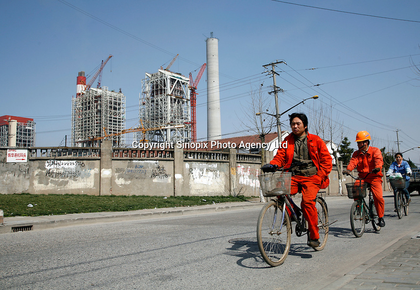 Workers bike past the still under construction third phase of a GD Power power plant on the outskirts of Shanghai, China..