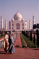 A view of the Taj Mahal as two Indian women in saris walk past. Agra, India.