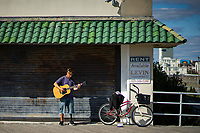 ATLANTIC CITY, NJ - OCTOBER 18: A man plays his guitar next to a poster for rent, on October 18, 2019 in Atlantic City, New Jersey.  Atlantic City has seen a resurgence, to its improved economy thanks to the launch of online gambling in the state. Sports betting, which kicked off last year, has also given the gaming industry a positive jolt. local media informed. (Photo by Eduardo MunozAlvarez/VIEWpress)