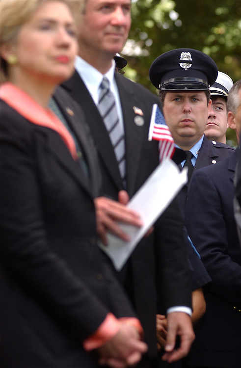 3ceremony101101 -- Sens. from left, Hillary Clinton, D-N.Y., and George Allen, R-Va., and unidentified police officers listen to speakers at a ceremony honoring those killed in terrorist attacks one month ago today.