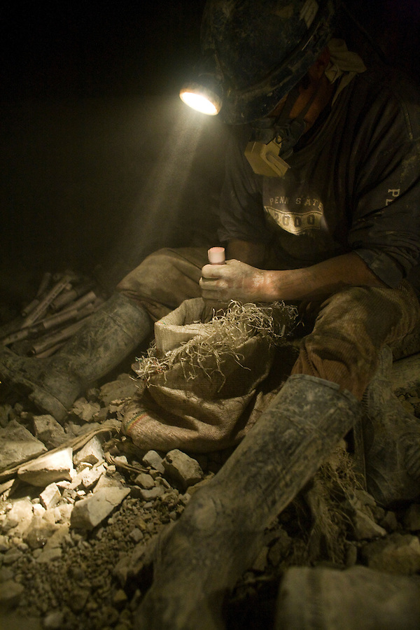 A miner in La Negra packing tubes of ammonium nitrate for blasting.