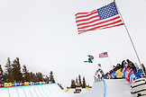 USA, California, Mammoth, a snowboarder launches out of the pipe during a competition at Mammoth Ski Resort