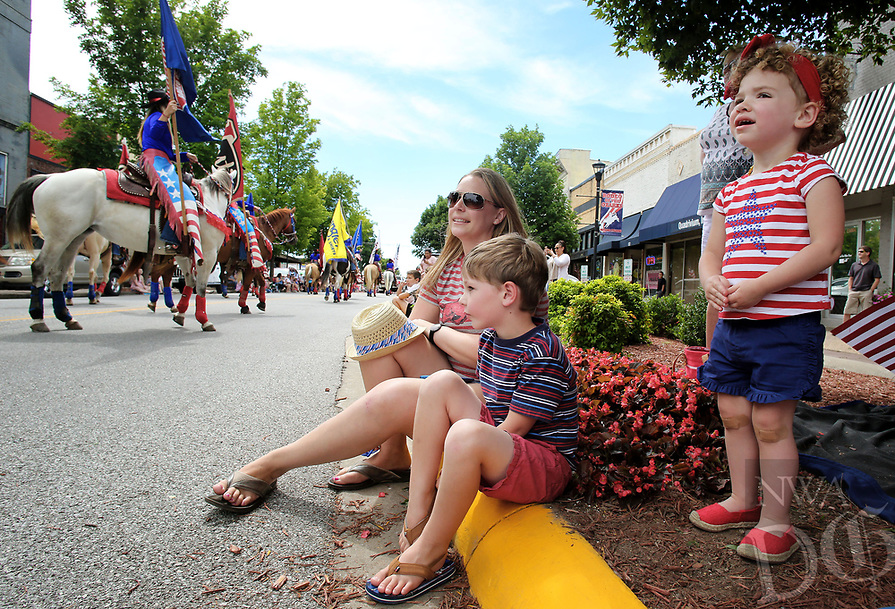 NWA Democrat-Gazette/DAVID GOTTSCHALK  Lucy Francis (from left), 2, Oliver Boseman, 4, and his mother Laura watch the Rodeo of the Ozarks Rounders Wednesday, June 21, 2017, as they participate in the annual Rodeo of the Ozarks Parade on Emma Avenue in Springdale. The parade kicks off the 73rd annual rodeo that opened Wednesday evening and runs through Saturday at Parsons Stadium.