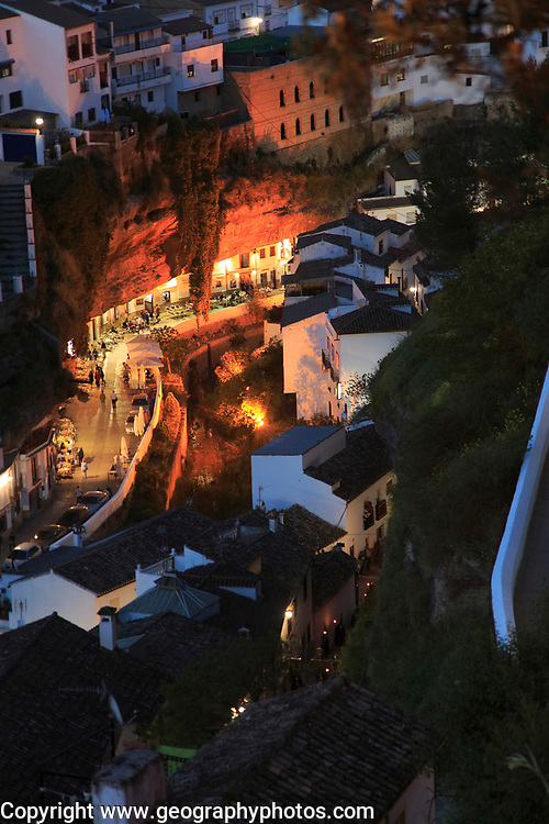 Cafes lit up at night under rock cave overhang, Setenil de las Bodegas, Cadiz province, Spain