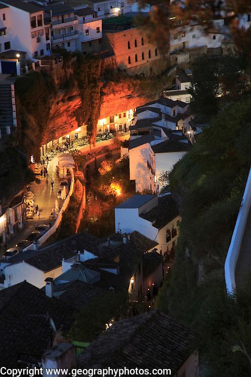Cafes lit up at night under rock cave overhang, Setenil de las Bodegas, Cadiz province, Spain