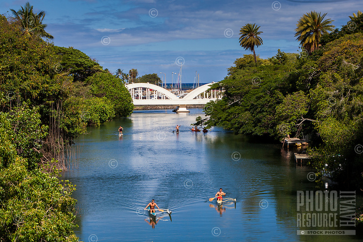 Kayakers and standup paddleboarders on Anahulu Stream in Haleiwa, North Shore, O'ahu.