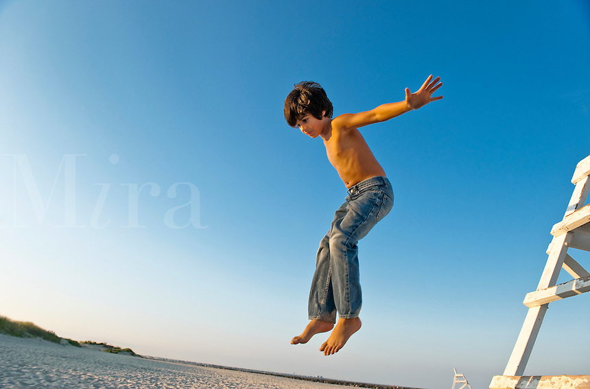 Boy jumping from a lifeguard stand.