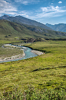A late June/early July rafting trip down the Marsh Fork of the Canning River through the Brooks Range in Alaska's Arctic National Wildlife Refuge features summer weather, moderate rapids, clear waters, great camping and awesome scenery. This is the view from the hills overlooking the river just downstream of a canyon; note the camp at right.
