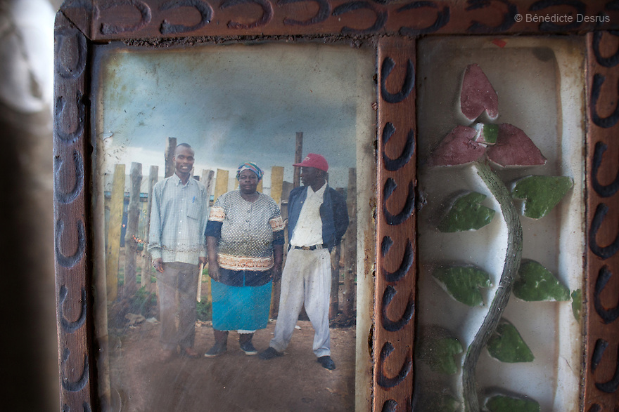 """An old photograph of """"Mama Safi"""" (C) with her son Musa (L) and her nephew Joshua (R), hang on the wall of her home inKawangware slum in Nairobi, Kenya on December 8, 2012. Susan Kalai aka """"Mama Safi"""" is a 53 year old Kenyan woman with severe morbid obesity living inKawangware slum in Nairobi, Kenya. Shelives on less than $1 USD a day, selling vegetables and fried potatoes in the street in front of her house. She has 7 children, the youngest one is 9 yearsold. She suffersfrom several obesity-related diseases. She can't walk, has a lot of pain in her legs and back and also has difficulties to breathe. She says """"I was born big. I was always like this.Both my parents and my sister are big too. So for me it's normal. Nothing is wrong with me"""".She has no knowledgeabout obesity and she can't go to the doctor to get treated because she has no money to pay for it. She is afraid to die of a heart attack. Although large parts of Africa areplaguedwith malnutrition, the continent must now also deal with another problem:obesity.Obesity is fast becoming a serious problem in Kenya and even the poorest are now being affected. Obesity rates are climbing around the world and they are rising faster in developing countries than in developed ones. (Photo by Benedicte Desrus)"""