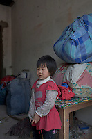 A young girl stands in front of her family's belongings as the family prepares to leave their home for good at Dawangjing Village which is being demolished on April 9, 2009 on the outskirts of Beijing, China. The local authorities are evicting residents, who are mainly migrant workers, to redevelop the area. The redevelopment of Beijing continues in high speed.