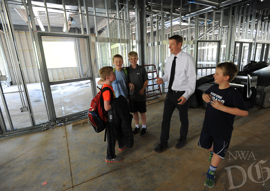 NWA Democrat-Gazette/ANDY SHUPE<br /> Phil Schwartz (center), head of the Upper School at The New School, leads a tour Wednesday, April 19, 2017, for a group of students in the school's Innovation Center during a beam raising and tour of the school's expansion project in Fayetteville. The New School hopes to open the facility in the fall for the 2017-18 school year.
