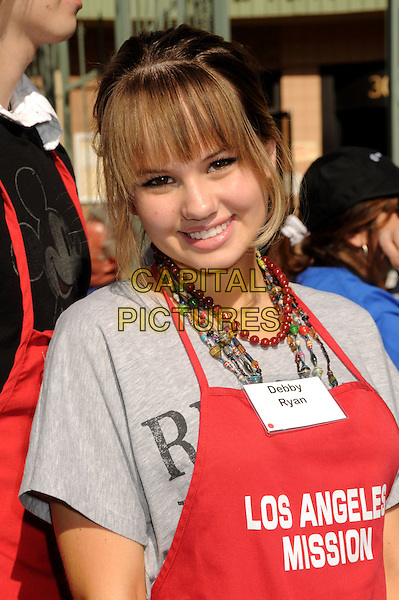 DEBBY RYAN .LA Mission & Anne Douglas Center's Thanksgiving Meal For The Homeless held at the Los Angeles Mission, Los Angeles, California, USA, .25 November 2009..Celebs celebrities doing charity work .portrait headshot red apron Debbie gloves beads necklaces fringe smiling grey gray t-shirt .CAP/ADM/BP.©Byron Purvis/Admedia/Capital Pictures
