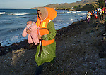 A refugee woman holds her baby as she walks along the coast after landing in an overcrowded rubber raft on a beach near Molyvos, on the Greek island of Lesbos, on October 30, 2015. She and the other refugees crossed the Aegean Sea from Turkey and were received by local and international volunteers. They then proceeded on their way toward western Europe. The boat was provided by Turkish traffickers to whom the refugees paid huge sums to arrive in Greece.