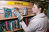 Young woman looking at a Video in a library,
