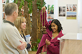 """A current student rattling a string of brazil nuts while showing a father & daughter around the exhibition, """"Heart of Brazil"""" by Sue Cunninham. The string of nuts is attached to the ankle whilst dancing.  Open Day at Kingston College when prospective students and their parents look around."""