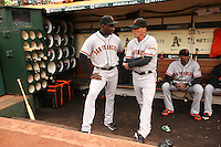 OAKLAND, CA - JULY 7:  Coaches Roberto Kelly #39 and Tim Flannery #1 of the San Francisco Giants talk in the dugout before the game against the Oakland Athletics at O.co Coliseum on Monday, July 7, 2014 in Oakland, California. Photo by Brad Mangin