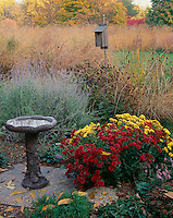Bureau County, IL:  Birdbath and garden of fall flowers at the edge of a tall grass prairie