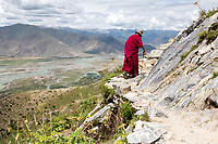 An elderly Tibetan monk walks along a trail which runs around a mountain near Lhasa, on top of which sits Ganden monastery. Pilgrims walk this trail around the sacred mountain which often narrows to no more than a foot wide at somepoints.