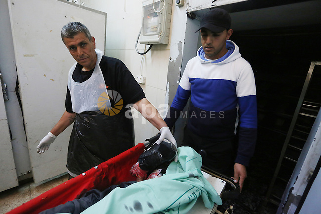 Palestinian relatives gather around the body of Abdallah Ghanayem, 22, at a hospital in the West Bank city of Ramallah, on June 14, 2015. Palestinian sources said that Ghanayem had been shot in the lower back during clashes in the village before the military jeep lost control and flipped on top of him on the sidewalk in the eastern Ramallah village of Kafr Malik. Photo by Shadi Hatem