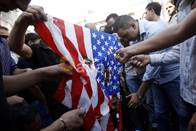 Palestinians burn the U.S. flag during a demonstration against the controversial film 'Innocence of Muslims' in the West Bank city of Nablus, on September 14, 2012. The controversial low budget film reportedly made by an Israeli-American which portrays Muslims as immoral and gratuitous, sparked fury in Libya, where four Americans including the ambassador were killed on Tuesday when a mob attacked the US consulate in Benghazi, and has led to protests outside US missions in Morocco, Sudan, Egypt, Tunisia and Yemen. Photo by Nedal Eshtayah
