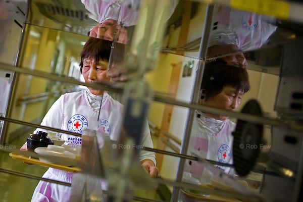 A Red Cross volunteer in Narita hospital outside Tokyo helps serve meals to elderly patients.