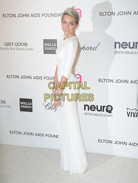 Miley Cyrus (wearing Azzaro).The 21st Annual Elton John AIDS Foundation Academy Awards Viewing Party held at The City of West Hollywood Park in West Hollywood, California, USA..February 24th, 2013.oscars full length dress white long sleeves diamond bracelets side backless .CAP/DVS.©DVS/Capital Pictures.