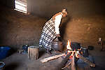 An old woman moving cooking pots on to her kitchen fire in a hut at her farm stockade in Pine Valley, Swaziland. The Kingdom of Swaziland (population 1.1m), a small, landlocked country in southern Africa was bordered by South Africa on three sides and Mozambique to the east, with Mbabane as its administrative capital. At the start of the 21st century, the country had the highest incidence per head of population of HIV/Aids in the world and and high levels of poverty mainly in rural areas where 75 per cent of the population lived.