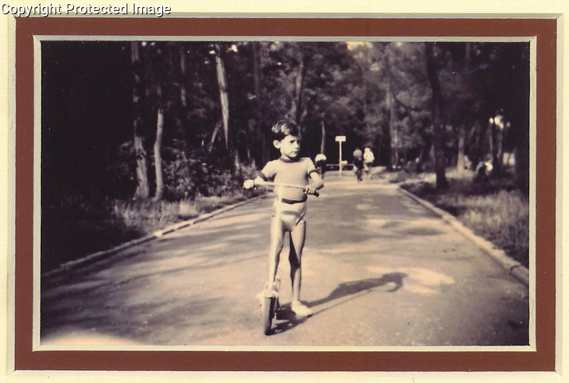 Young Guy Buffet in Paris at Age 5 in 1948, riding his scooter in the park.