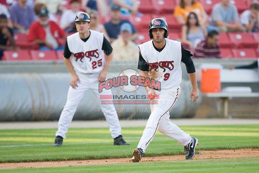 Eric Eymann #9 of the Carolina Mudcats takes his lead off of third base as Carolina Mudcats manager David Bell #25 looks on at Five County Stadium May 15, 2010, in Zebulon, North Carolina.  Photo by Brian Westerholt /  Seam Images