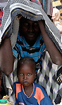 A Somali man shelters his child as he waits to be assigned a new tent in an extension of the world's largest refugee settlement. Swelled with tens of thousands of recent arrivals fleeing drought in Somalia, the Dadaab camp in northeastern Kenya has been unable to absorb the newest arrivals. The Lutheran World Federation, a member of the ACT Alliance, is manager of the camp and in July began moving hundreds of families into tents in the extension.