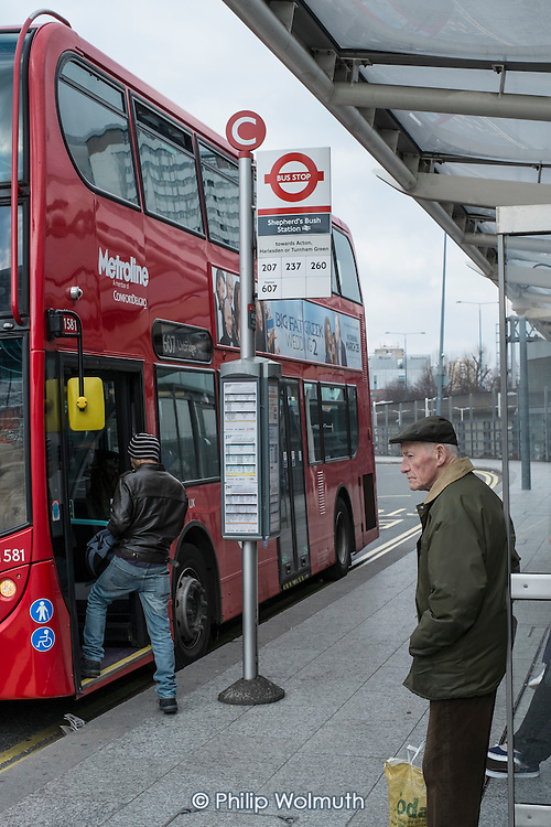 Elderly man waiting at a bus stop, Shepherds Bush, London