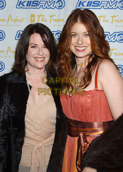 MEGAN MULLALLY & DEBRA MESSING.The Trevor Project's 'Cracked XMAS 7' held at the Wiltern LG..December 5th, 2004.half length, pearl necklace, orange, brown ribbon belt, orange dress, black fur.www.capitalpictures.com.sales@capitalpictures.com.© Capital Pictures.