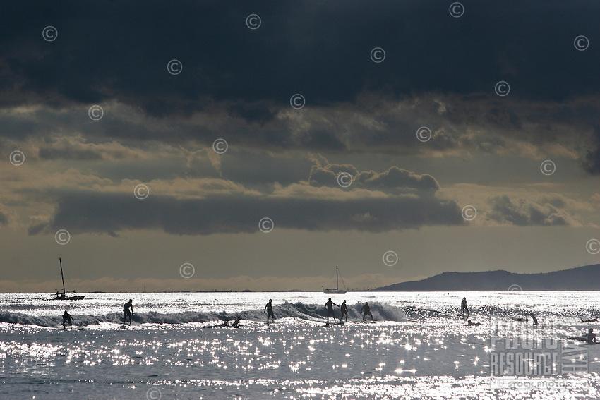 Surfers ride the small break outside of Waikiki on Oahu