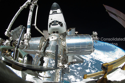 A portion of the International Space Station and the docked space shuttle Endeavour is featured in this image photographed by a spacewalker, using a fish-eye lens attached to an electronic still camera, during the STS-134 mission's fourth session of extravehicular activity (EVA) on May 27, 2011. The blackness of space and Earth's horizon provide the backdrop for the scene..Credit: NASA via CNP