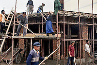 Workers construct a building in Xiahe, Gansu, China. Xiahe, home of the Labrang Monastery, is an important site for Tibetan Buddhists.  The population of the town is divided between ethnic Tibetans, Muslims, and Han Chinese.