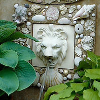 Water flows from a lion's mouth mounted on the wall of the pavilion which is decorated with shells