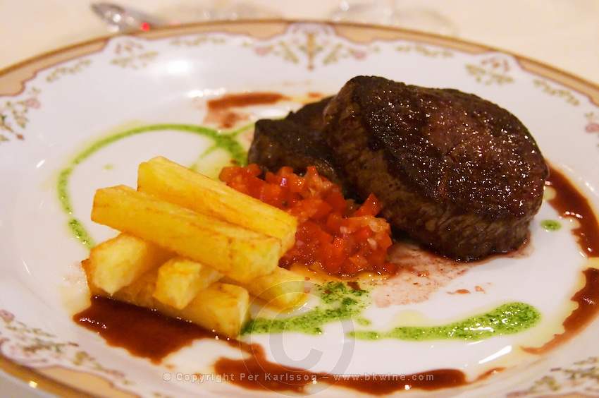 In the Sheraton Hotel Restaurant a dish of French fries potatoes stacked in a pile and tomato sauce and a grilled steak. Buenos Aires Argentina, South America