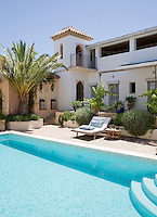 A swimming pool lined with turquoise mosaic tiles in the spacious courtyard