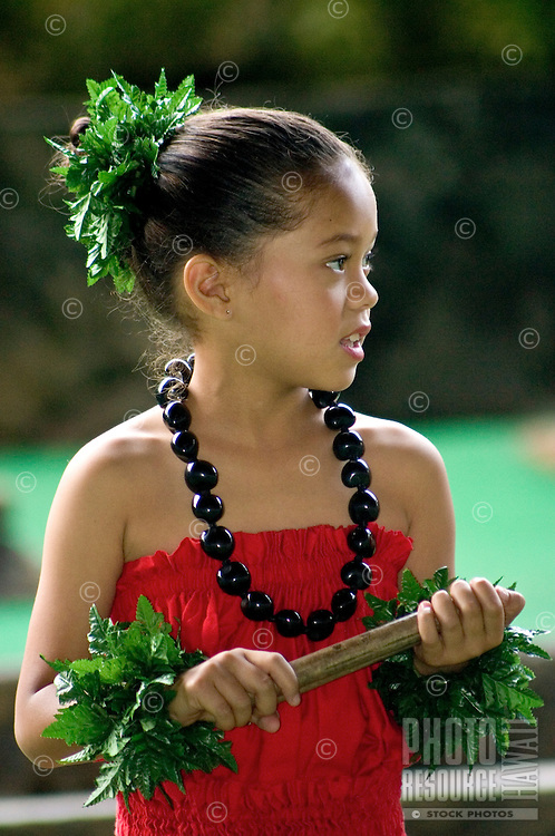 Profile portrait of young girl waiting to start a hula number. Wearing red dress and kukui nut lei.
