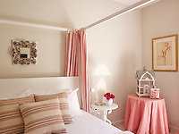 A tiny elaborately carved antique mirror and Rococo-style bedside table add simple feminine touches to this pretty bedroom