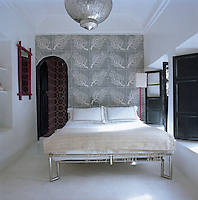 The chrome-framed bed, silver lantern and bold patterned wall tiles by Popham Design create a striking bedroom