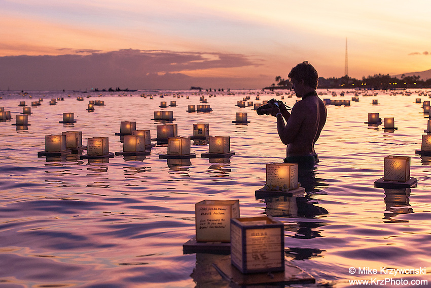 Man photographing lanterns floating in the water during the 15th Annual Lantern Floating Ceremony at Ala Moana Beach Park in Honolulu on Memorial Day
