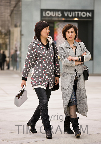 Women outside Louis Vuitton deisgner clothes shop, on Nanjing Road, central Shanghai, China