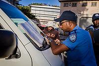 Der Kapstädter Polizist Enrico Pillay schreibt den Strafzettel für den Fahrer eines Minibus-Fahrers, der in der Kapstädter Innenstadt eine Strecke gefahren ist, für die er keine Genehmigung hatte.