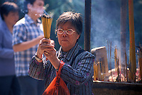 Worshipper with joss-sticks at the city's HuaLin Temple, Guangzhou, Guangdong Province, China.   .2004