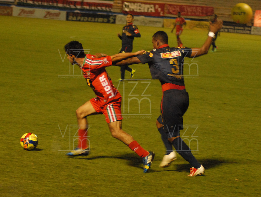 TUNJA - COLOMBIA -13 -03-2014: Hugo Bolaños (Izq.) jugador de Patriotas FC disputa el balón con Luis Lipton (Der.) jugador de Deportivo Independiente Medellin, durante partido por la decima fecha  de la Liga Postobon I-2014, jugado en el estadio La Independencia de la ciudad de Tunja. / Hugo Bolaños (L) player  of Patriotas FC vies for the ball with Luis Lipton (R) player of Deportivo Independiente Medellin, during a match for the tenth date of the Liga Postobon I-2014 at the La Independencia  stadium in Tunja city, Photo: VizzorImage  / Jose M. Palencia / Str. (Best quality available)