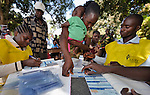 Holding her baby, Victoria John Toro puts her fingerprint on a registration document as citizens of Southern Sudan lined up on November 15, the first day of a 17-day registration period in preparation for the January 2011 referendum on secession from the north of the country. Toro registered to vote at a registration center located in a Catholic school in Yambio, in Western Equatoria State. NOTE: In July 2011 Southern Sudan became the independent country of South Sudan.