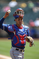 OAKLAND, CA - APRIL 23:  Robinson Chirinos #61 of the Texas Rangers works behind the plate against the Oakland Athletics during the game at O.co Coliseum on Wednesday, April 23, 2014 in Oakland, California. Photo by Brad Mangin