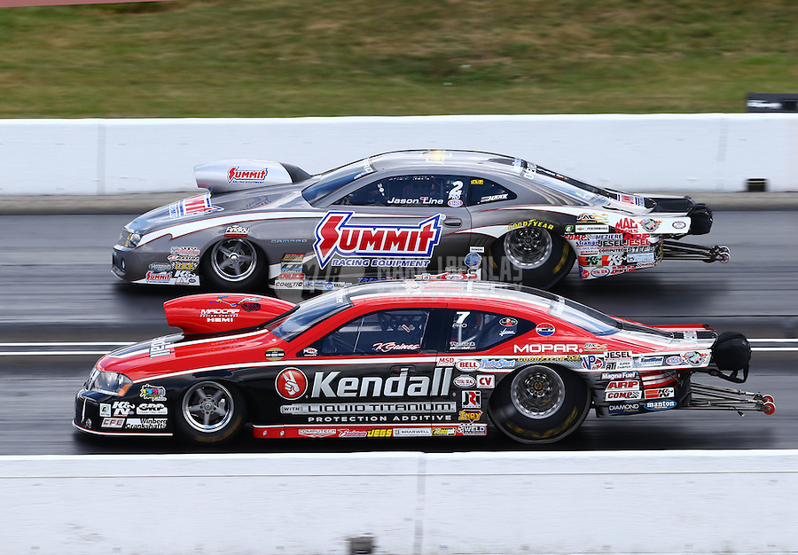 Sept. 2, 2013; Clermont, IN, USA: NHRA pro stock driver V. Gaines (near) races alongside Jason Line during the US Nationals at Lucas Oil Raceway. Mandatory Credit: Mark J. Rebilas-