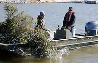 NWA Democrat-Gazette/DAVID GOTTSCHALK  Kevin Hopkins (left) and Jon Stein, fisheries biologist with the Arkansas Game and Fish Commission, drop a Christmas tree Wednesday, January 13, 2016, tethered to a cinder block  from a 22 ft. boat into Lake Elm Dale east of Springdale. The donated trees are dropped into the lake as part of the  Christmas Tree Habitat Program.